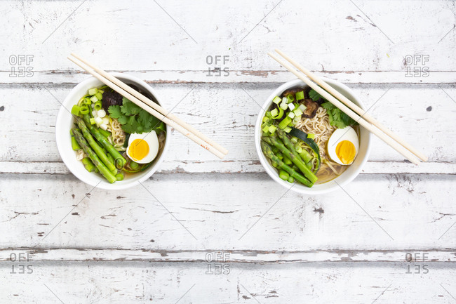 Two bowls of Ramen soup with egg- green asparagus- noodles- shitake mushroom and spring onions