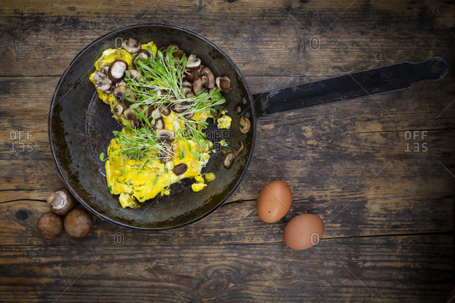 Omelet with champignon and fresh cress in pan