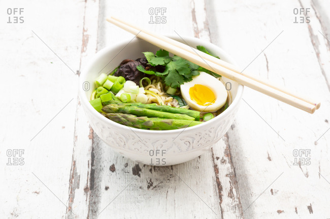 Bowl of Ramen soup with egg- green asparagus- noodles- shitake mushroom and spring onions