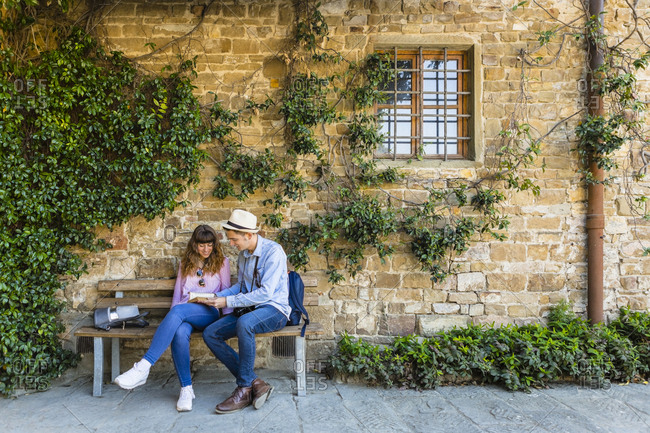 Young couple on a city break- sitting on a bench- taking a break