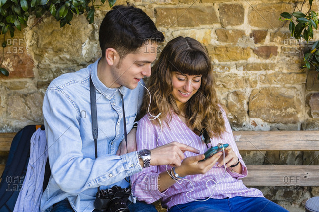 Young couple on a city break- sitting on a bench- using smartphone