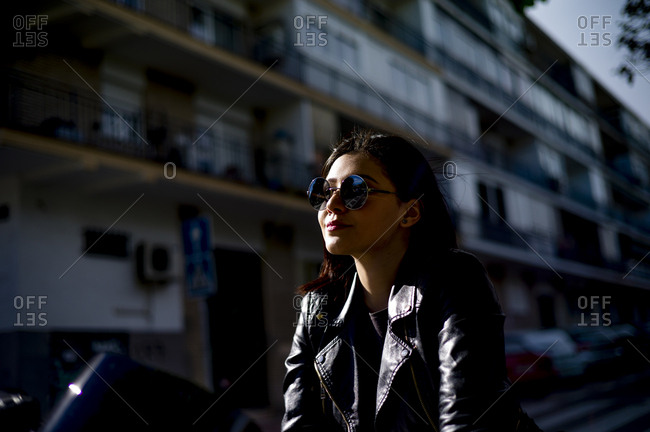 Portrait of young motorcyclist wearing sunglasses at evening twilight