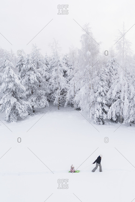 Finland- Kuopio- mother and daughter with sledge in winter forest