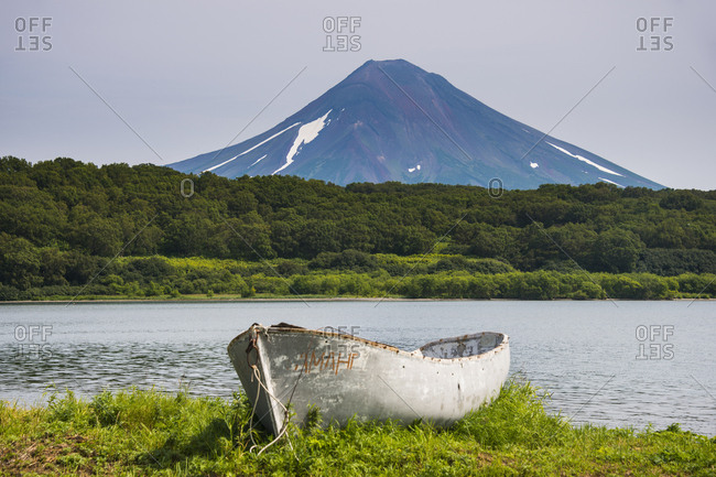 August 14, 2013: Russia- Kamchatka- Wooden canoe before the Ilyinsky volcano and Kurile lake