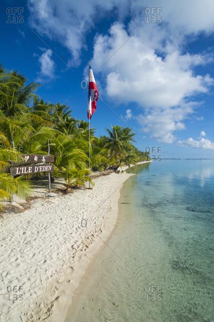 May 17, 2016: French Polynesia- Tuamotus- Tikehau- palm beach with flag