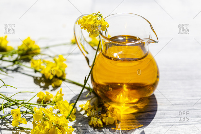 Rapeseed oil in jar with rape blossom on wood