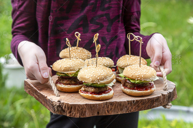 Girl holding wooden tray with mini burger