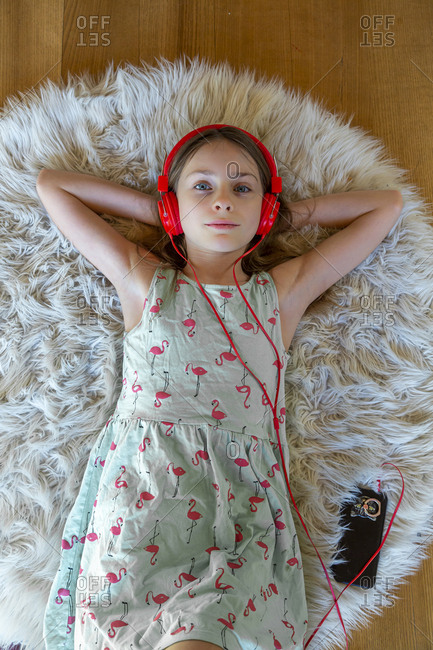 Girl lying on carpet at home listening to music with headphones and smartphone