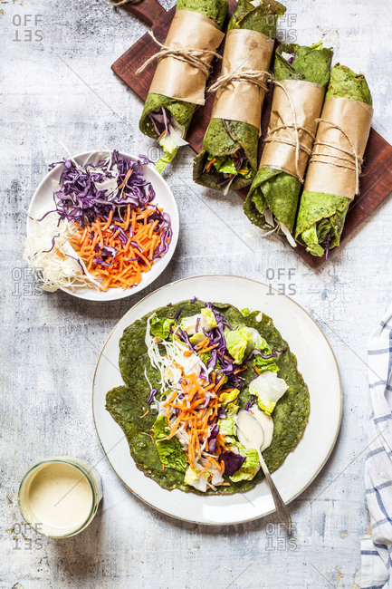 Lettuce wraps with spinach tortillas filled with lettuce- carrots and salad dressing