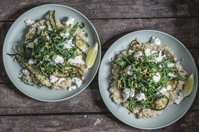 Two plates of lemon risotto with Buffalo Mozzarella- rocket- baked courgette and pine nuts