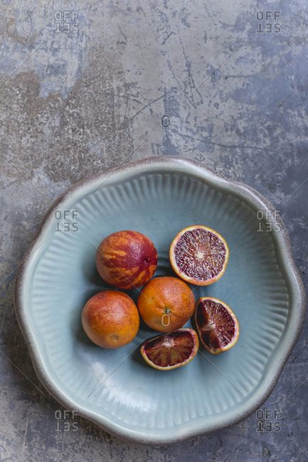 Whole and sliced blood oranges in a bowl