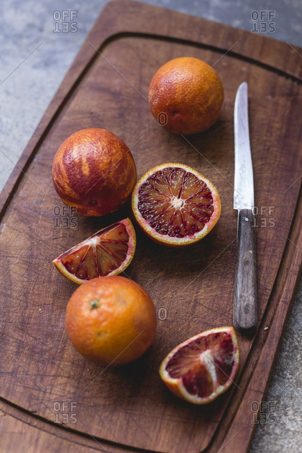 Whole and sliced blood oranges and a kitchen knife on wooden board