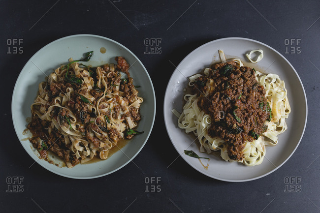 Two plates of Tagliatelle with spinach Bolognese sauce