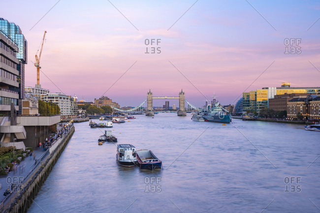 UK- London- The Tower Bridge with the HMS Belfast at sunset with purple sky