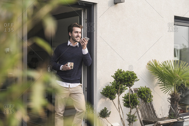 Young man leaning in door of his house- holding cup of coffee- using smartphone