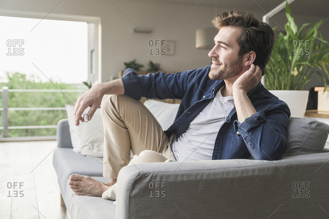 Young man sitting on couch at home- looking out of window