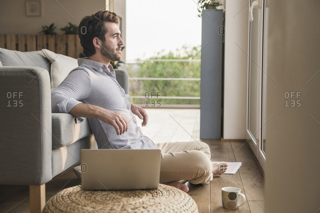 Young man sitting at home on floor- using laptop- looking out of window