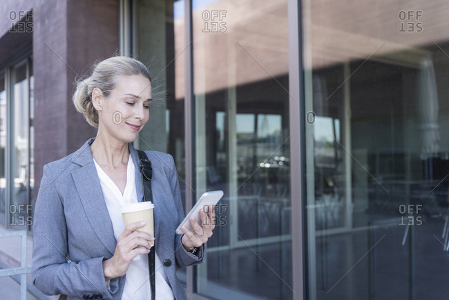 Businesswoman with cell phone and takeaway coffee on the go in the city