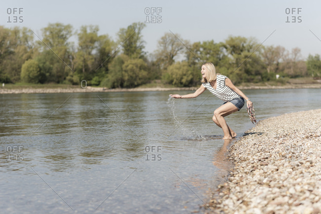 Happy mature woman splashing in a river
