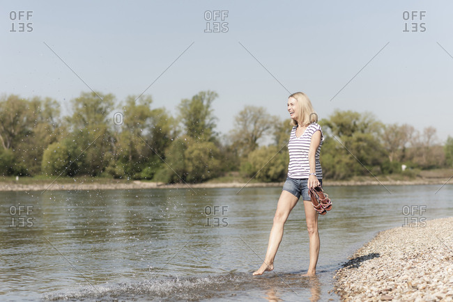 Carefree mature woman splashing in a river