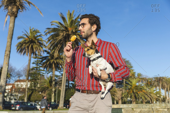 Young man with dog on his arm eating ice lolly