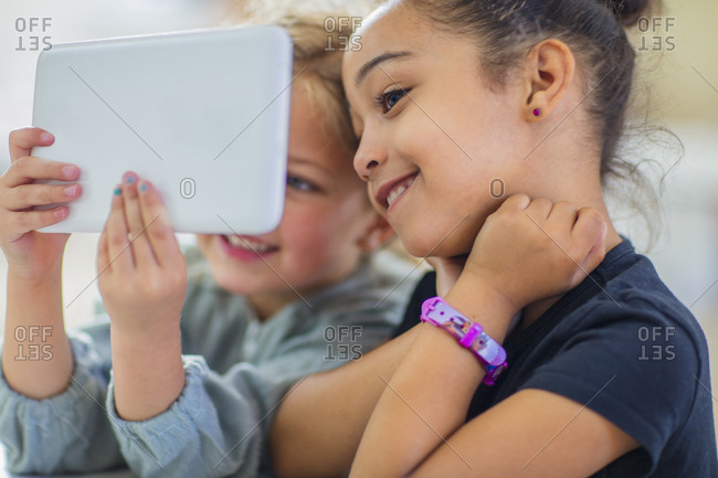 Two smiling girls sharing mini tablet in kindergarten