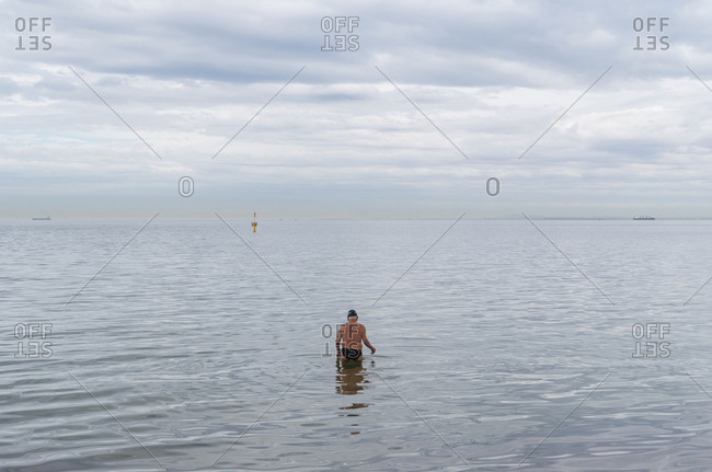 Man wading into the ocean for a morning swim