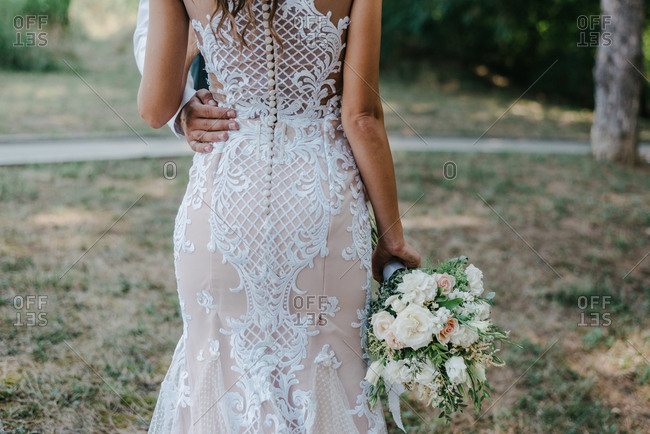 Beautiful bride in elegant white wedding dress holding bouquet while groom is holding her hip