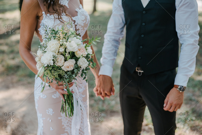 Bride and groom holding hands while standing outside