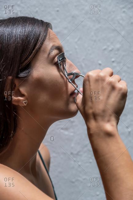Brunette woman using eyelashes curler