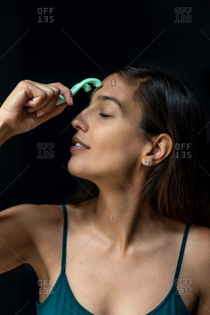 Brunette woman using a facial massager