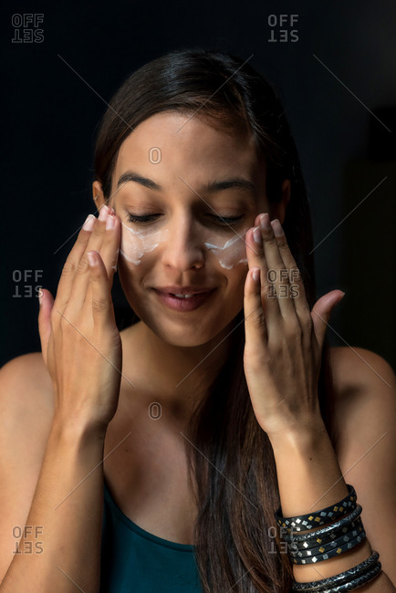 Brunette woman putting face cream
