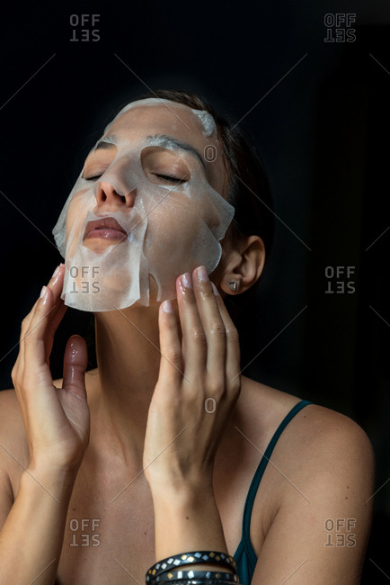 Brunette woman with a sheet moisturizing mask on her face