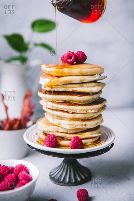 Syrup being poured over tall stack of pancakes with raspberries
