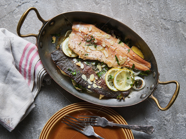 Cooked trout in pan with almonds lemon and parsley