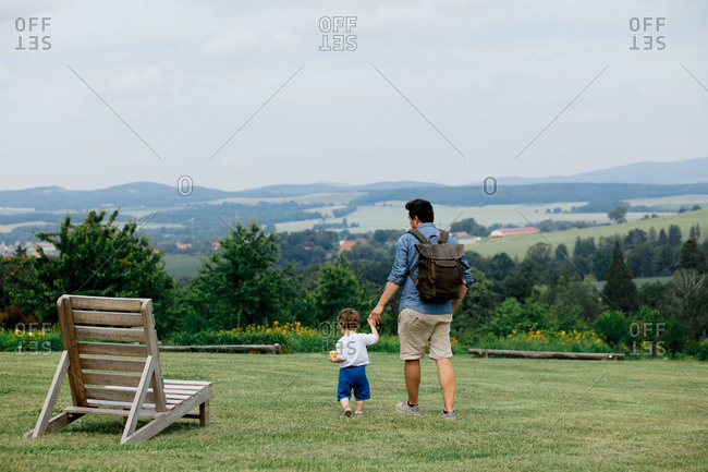 Father and son holding hands while walking through a park