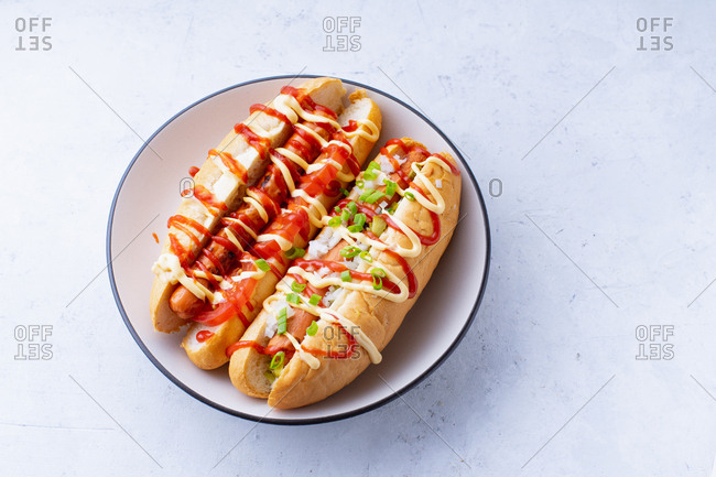 Two grilled hot dogs with condiments and toppings