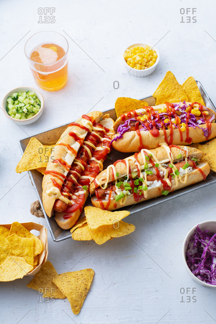 Three dressed hot dogs with various fresh toppings