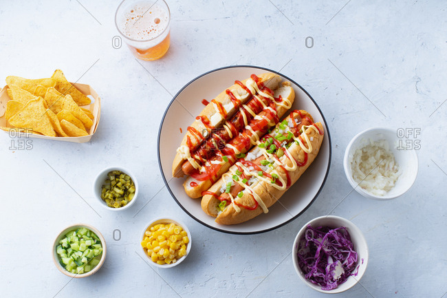 Overhead view of two hotdogs and various bowls of toppings
