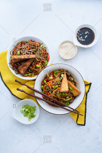 Asian-styled lunch with vegetarian soba noodles with fried vegetables, edamame beans and tofu