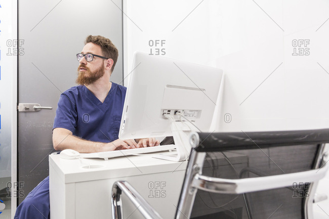 Male redhead veterinarian consults patient data in the computer