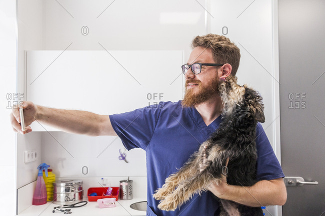 Smiling male redhead veterinarian poses and takes a selfie with a puppy in veterinary practice