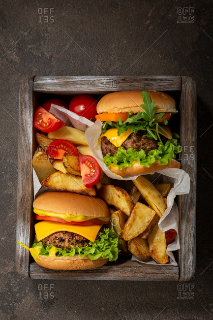 Hamburgers with cheese and beef in wooden crate