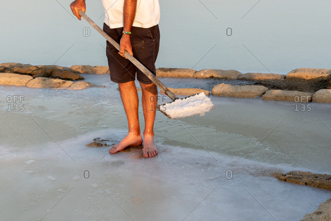 Man shoveling salt from salt flats in Trapani, Sicily, Italy