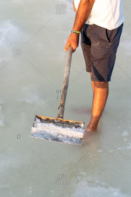 Man scooping salt from salt flats in Trapani, Sicily, Italy