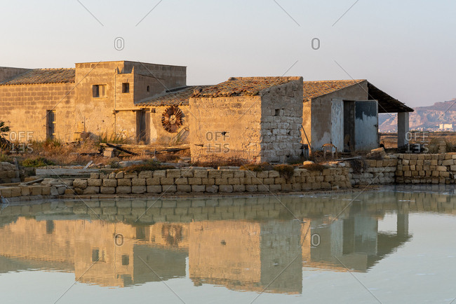 Stone buildings reflecting in salt flats, Trapani, Sicily, Italy