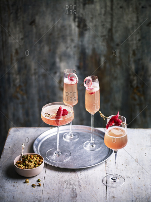 Four glasses of rhubarb prosecco cocktail fizz with tray and a bowl of nuts on the side