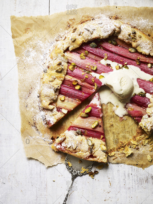 A rhubarb galette with a scoop of vanilla ice cream and slice taken away
