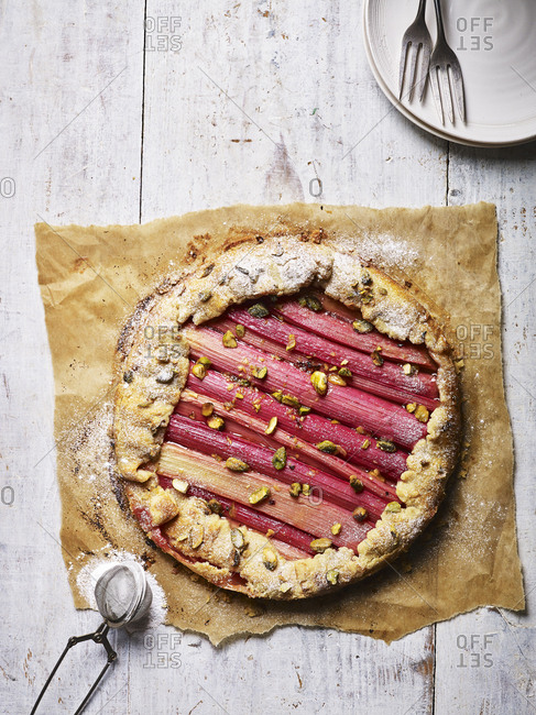 A rhubarb galette whole, and fresh out the oven with icing sugar sprinkled on it
