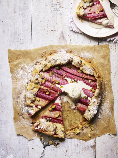 A rhubarb galette with a scoop of vanilla ice cream and serving on the side